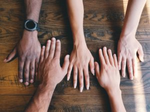 five hands of different races resting on a wooden table