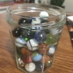 jar filled with marbles sitting on a table