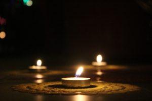 three votive candles lit in the dark